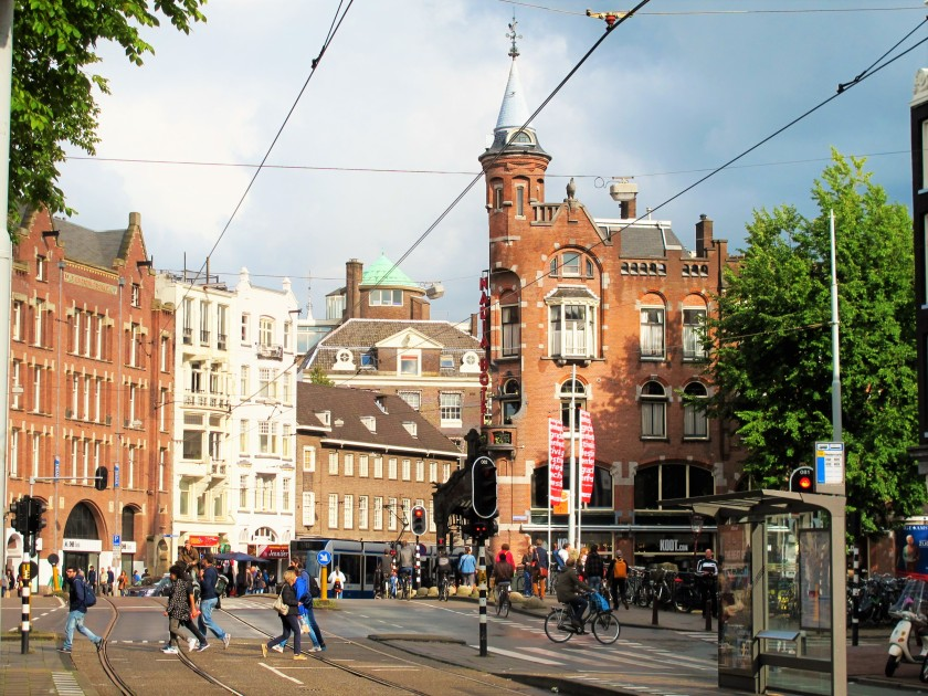 An avenue in Amsterdam with old buildings, lots of people, a tram station and rails, and lots of people.