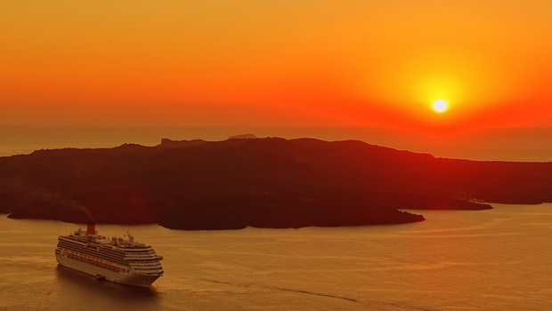 Cruise ship in foreground, island in midground, setting sun in background