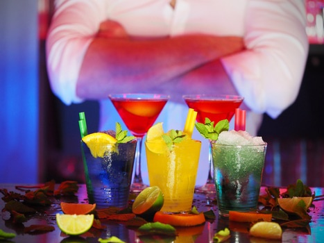 An array of cocktails on a bar table, with a bartender in the background