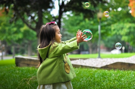 Female toddler trying to catch a bubble in a park