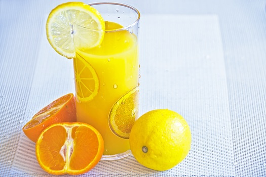 Glass of orange juice, and slices of oranges and lemons