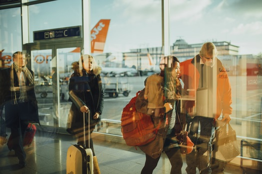 Passengers walking past an airport gate