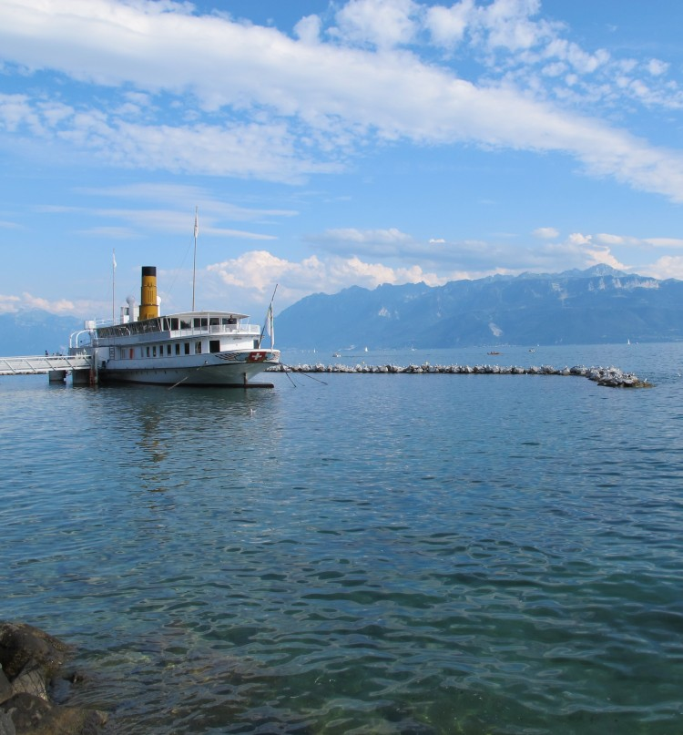 A ship temporarily housing the Olympic Museum in Lausanne is docked in the calm blue waters of Lake Geneva, against a backdrop of blue skies and mountains