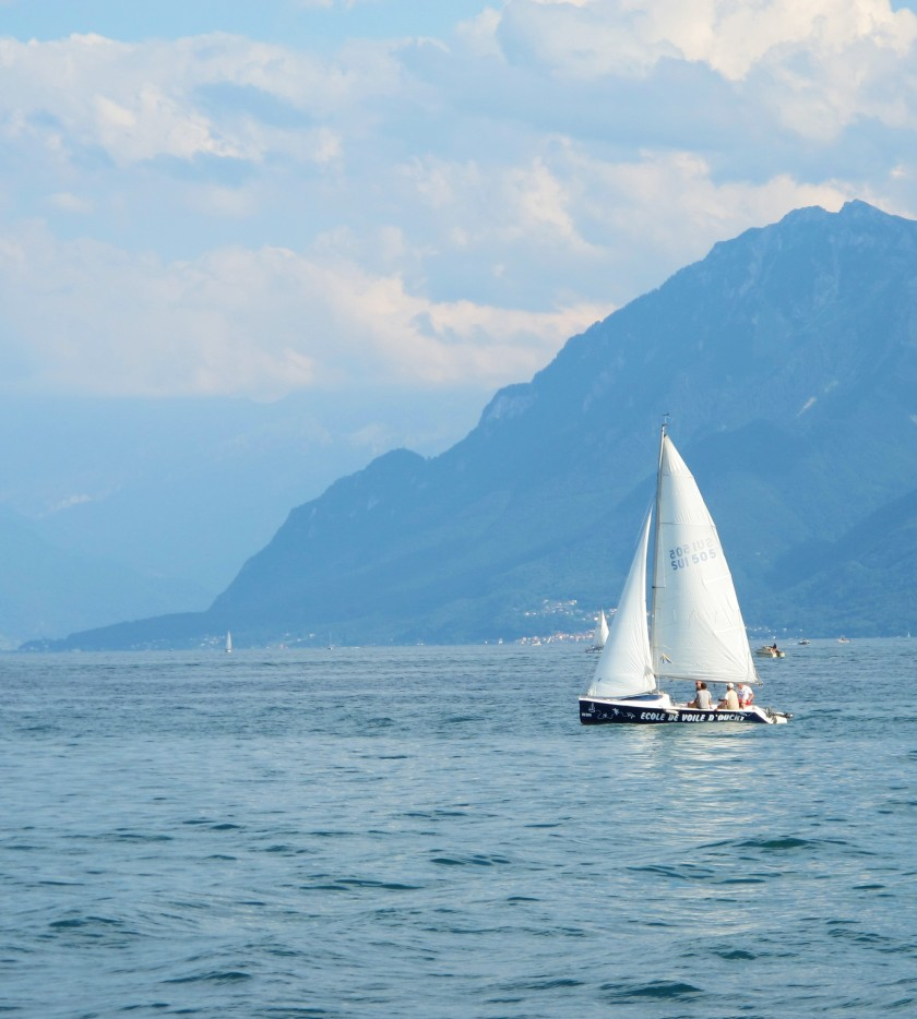 A sailboat in Lake Geneva near Lausanne, against a mountainous cloudy backdrop