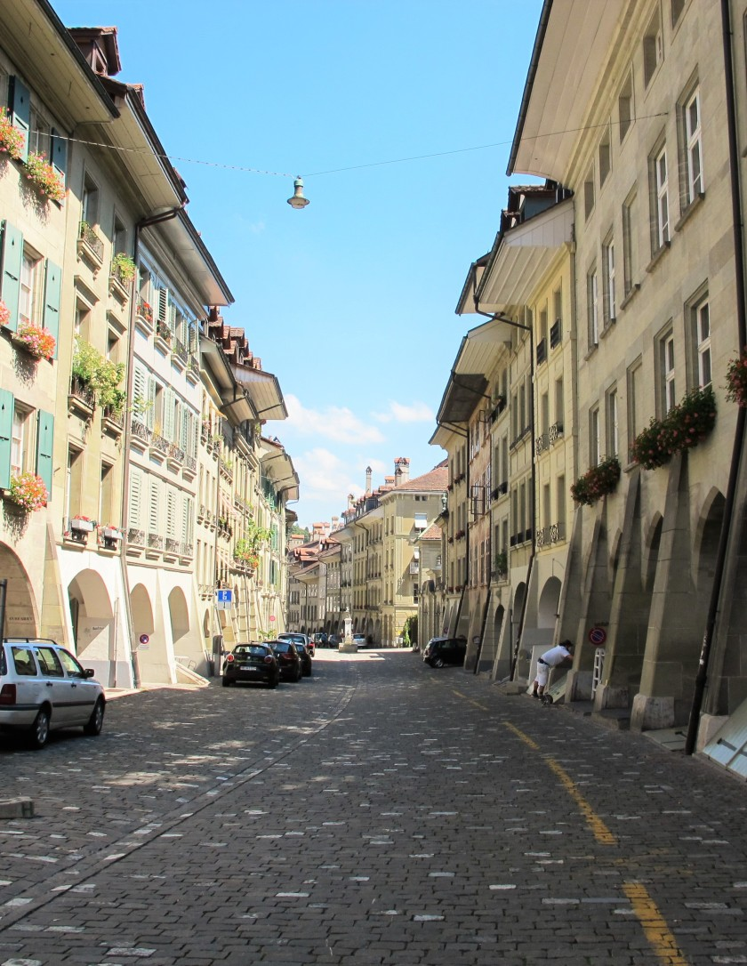 An empty street in Bern with cobblestones, cars, and classic architecture