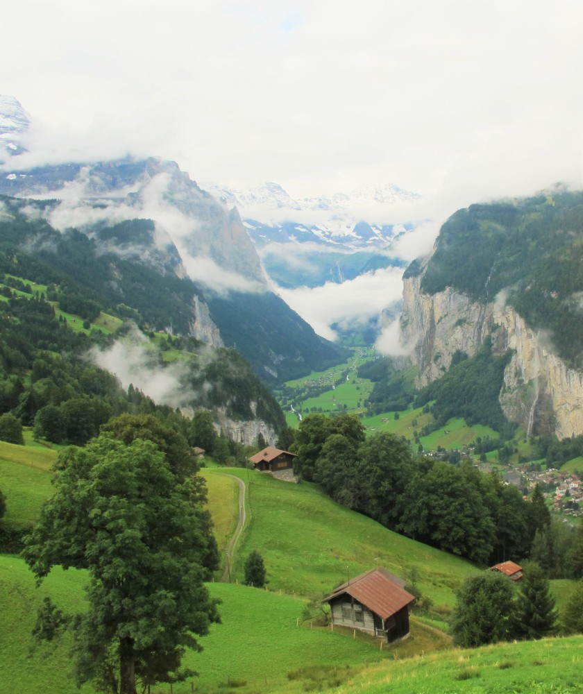 Rolling green hills dotted with homes, trees, and mountains shrouded with mist on the way up to the Jungfrau in Interlaken, Switzerland