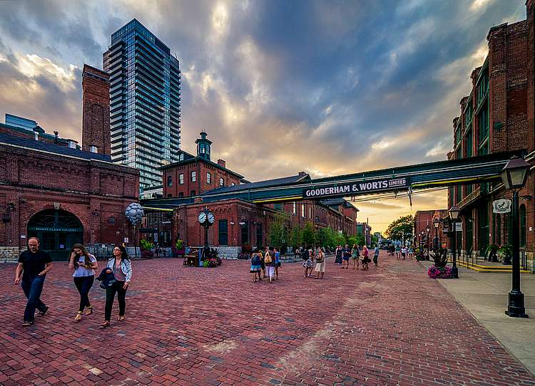 The Toronto Distillery District on a cloudy day, with buildings in the background and busy shoppers in the foreground